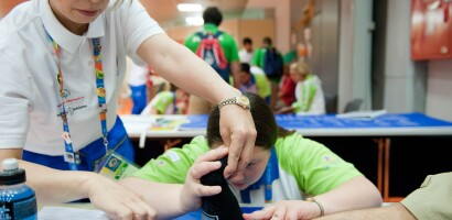A Volunteer Conducts a Healthy Athletes Fit Feet Exam on the Foot of a Patient at the World Summer Games, Athens, Greece, 2011
