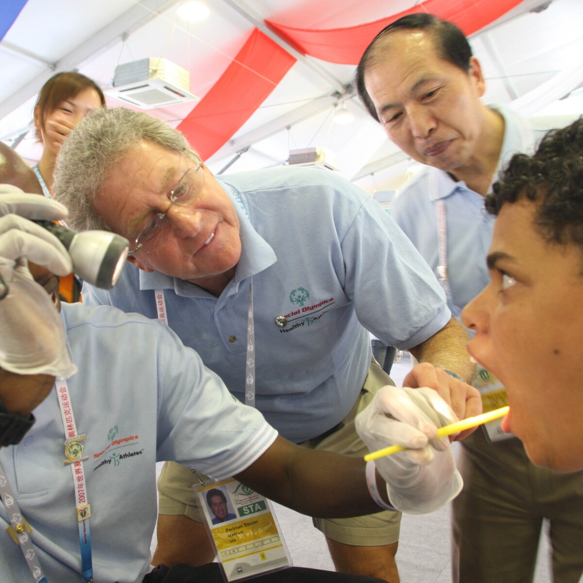 Healthy Athletes Program Founder, Dentist Dr. Steve Perlman, Performs a Special Smiles Dental Examination with Others at the 2007 World Summer Games in Shanghai, China