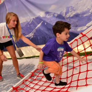 "Toys ""R"" Us Volunteer with Boy Climbing on Rope Obstacle at Young Athletes Event, USA Games, 2014"